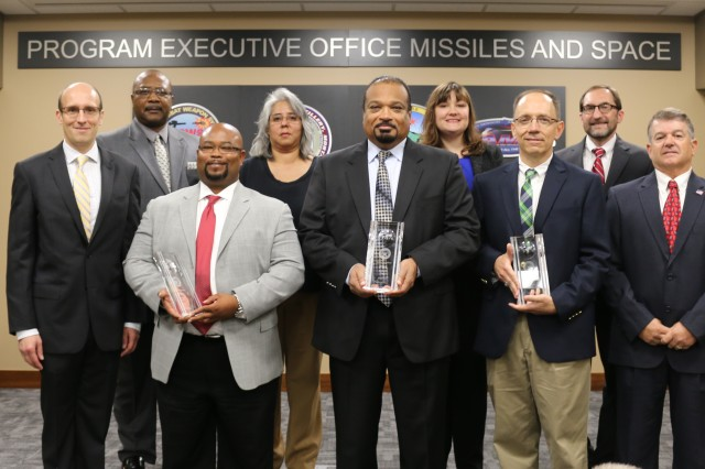 Terrence Emmert, deputy assistant Secretary of Defense for Materiel Readiness, first row at left; and Barry Pike, program executive officer for Missiles and Space, second row at right, congratulate the Javelin Joint Venture Performance-Based Logistics Team for winning a Secretary of Defense Performance-Based Logistics Award during the award presentation on July 26 at the headquarters for the Program Executive Office for Missiles and Space. Representing the government-contractor team are, front row from left, Walter Jones (Raytheon), Tyrone Smith (Lockheed-Martin), and Steven Potts and Barry Thrower of Close Combat Weapons Systems, PEO for Missiles and Space; and second row from left, Phillip Epperson, T.J. Longoria and Autumn Knoth-Jez, all of Close Combat Weapon Systems.