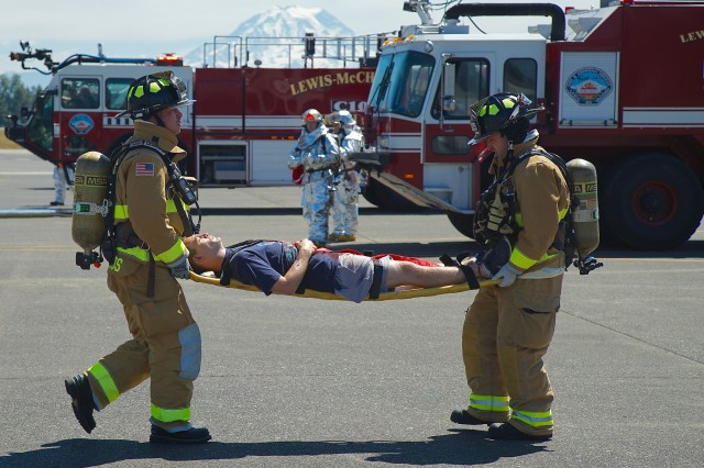 Firefighters from Fire Station 105, McChord Field, Joint Base Lewis-McChord move a casualty away from danger during exercise Cascade Helix, a force protection and mass casualty exercise July 26, 2016.