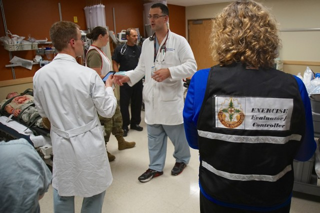 Madigan Army Medical Center staff coordinate as the injured arrive and an exercise evaluator looks on at MAMC Joint Base Lewis-McChord July 26, 2016.