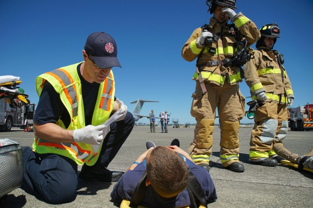 Fire and medical personnel evaluate a casualty during exercise cascade Helix at Joint Base Lewis-McChord July 26, 2016.