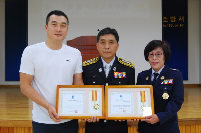 After an awards ceremony at a fire station in Dongducheon July 22, Area I Firefighter Chong Sung-ho (left) displays the medal presented him for using his firefighter life-saver training to help a man who'd collapsed with a heart attack June 26 at an apartment complex in Dongducheon. Chong is assigned to the U.S. Army Garrison Red Cloud and Area I's fire station on Warrior Base in Paju. At right is Kong Soon-yeol, who at one point joined Chong in aiding the stricken man. Kong is head of the Dongducheon Fire Department's Female Auxiliary. During the ceremony, Dongducheon City Fire Chief Kwon Yong-han (center) presented each a medal for their aid to the man. -- Photo courtesy of Dongducheon City Fire Department