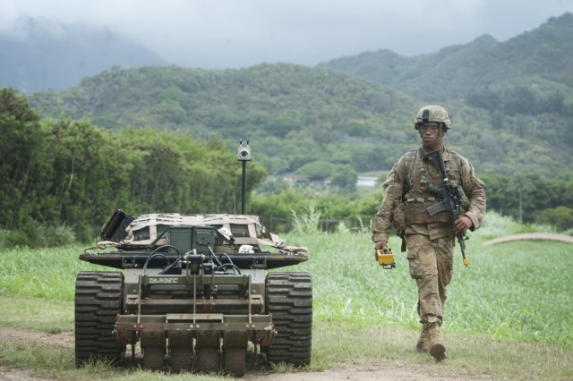 An Army Pacific Soldier moves down a road while controlling an unmanned vehicle as part of the Pacific Manned Unmanned -- Initiative on July 22 at Marine Corps Training Area Bellows, Hawaii.