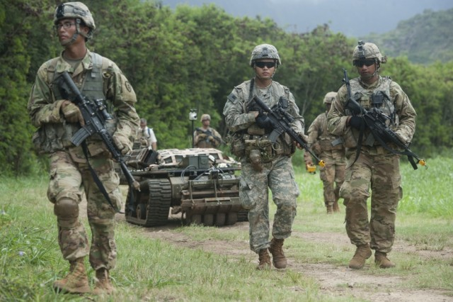 Army Pacific Soldiers, 25th Infantry Division, move in formation while controlling unmanned vehicles as part of the Pacific Manned-Unmanned Initiative on July 22 at Marine Corps Training Area Bellows, Hawaii.