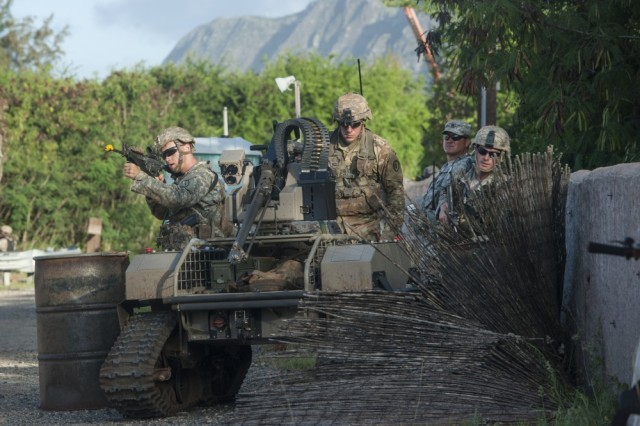 Army Pacific Soldiers, 2nd Battalion, 27th Infantry Regiment, 3rd Brigade Combat Team, 25th Infantry Division, move forward toward simulated opposing forces with a Multipurpose Unmanned Tactical Transport (MUTT) during the Pacific Manned-Unmanned Initiative on July 22 at Marine Corps Training Area Bellows, Hawaii.