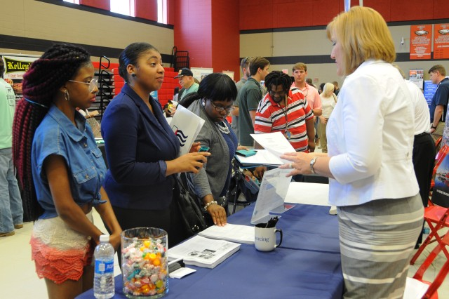 Job seekers speak with employers during the 13th annual Fort Rucker Area Job Fair at the Carroll High School Gymnasium in Ozark July 21.