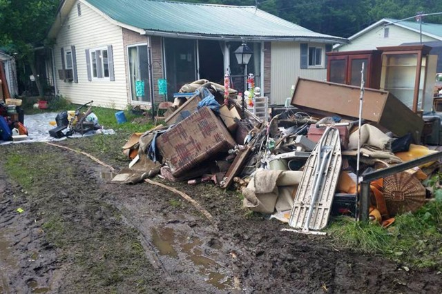 A pile of furniture, carpeting and assorted personal items destroyed by flood water sits in front of the Cook family's home in Leslie, West Va. The family has measured the water line at 44 inches outside the structure and 20 inches inside.