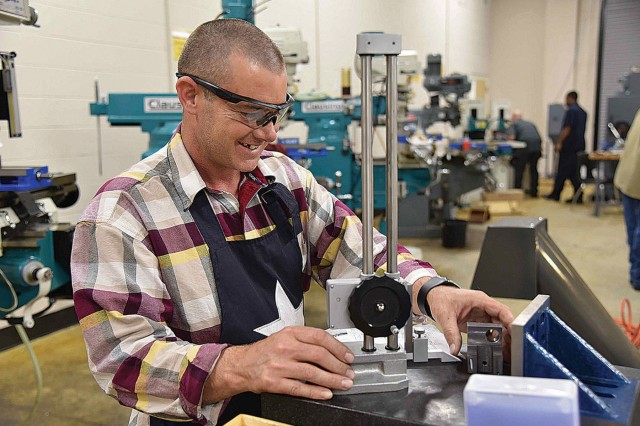 Machinist student Jason Cates works with a precision-height gauge to lay out a fabrication for his project.