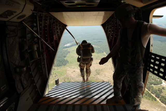 "A U.S. Army Special Operations Command Paratrooper exits from the ramp of a Casa 212 aircraft after receiving the command of ""Go!"" from a student (right) during the culminating event of the course, July 27. Of the 40 Paratroopers who began the course, led by 4th Military Information Support Group jumpmasters, only 23 completed it successfully. The course concentrates on the actions taken on the ground and in the air to safely exit Paratroopers from a number of different aircraft. (U.S. Army photo by Staff Sgt. Kissta DiGregorio/Released)"