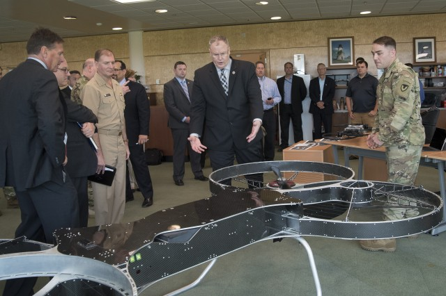 Deputy Secretary of Defense Robert O. Work (center) asks questions about the Joint Tactical Aerial Resupply Vehicle, or JTARV, a rectangular-shaped quadcopter that currently carries up to 300 pounds of cargo.