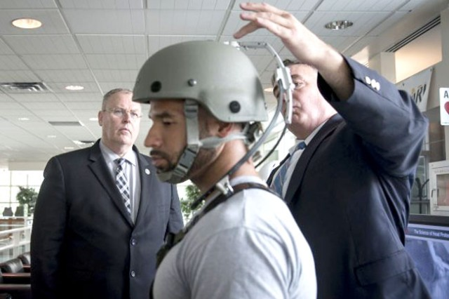 Deputy Secretary of Defense Robert O. Work (left) learns about the Vertical Load Offset System, a device designed to lighten the load by shifting a helmet's weight to the shoulders from Army materials scientist Dr. Shawn Walsh (right) and Army Research Laboratory technician Mike Thompson (center) during an Aug. 2 visit to Aberdeen Proving Ground, Maryland.