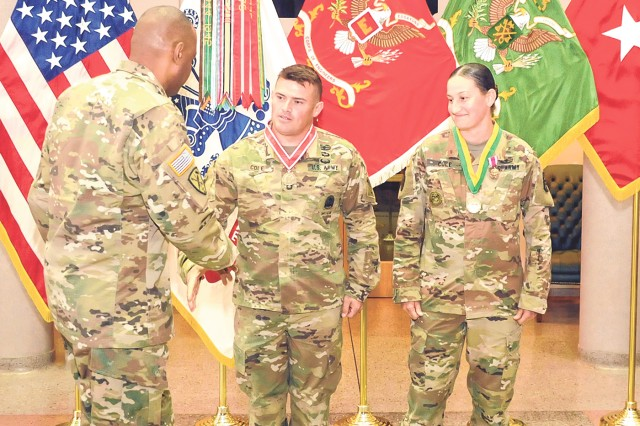 Sgt. 1st Class Jeremy Cole, Sapper School instructor, center, and his wife, Sgt. 1st Class Johanna Cole, 795th Military Police Battalion tactical sergeant, right, are congratulated by Brig. Gen. Kevin Vereen, U.S. Army Military Police School commandant, following an award presentation where Jeremy was presented with the Bronze Order of the de Fleury medal and Johanna was presented the Bronze Order of the Marechaussee medal, both for significant contributions to their respective regiments during their time at Fort Leonard Wood.