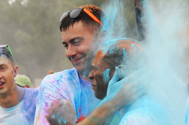 Runners get hit with a barrage of powdered color as volunteers toss clouds of different hues during last year's inaugural Color Run.