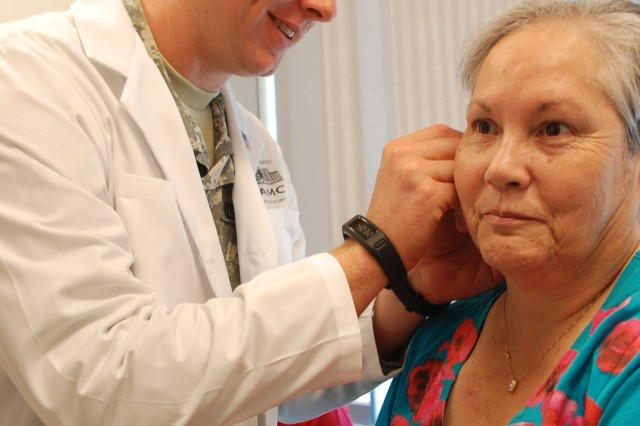 Maj. (Dr.) R. Anderson, Internal Medicine physician, inserts acupuncture needles in Nelda Rodriguez's ears to relieve pain from her neck at Brooke Army Medical Center.