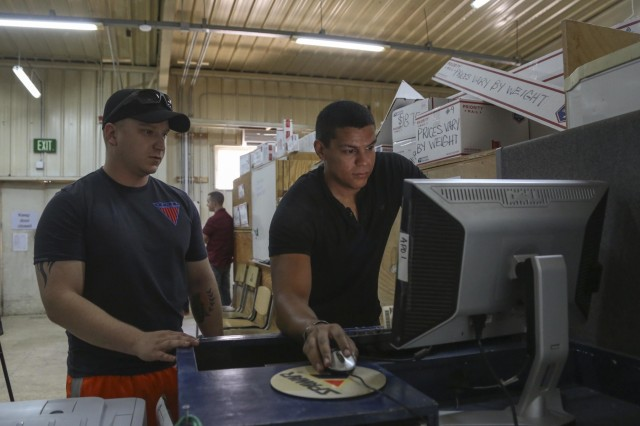 Cpl. Federico Jarrett, right, an Army Reserve mail clerk with the 4th Platoon of the 912th Human Resource Company, 90th Human Resource Company, 17th Special Troops Battalion, 17th Sustainment Brigade, 1st Sustainment Command (Theater), helps Spc. Jesse Dzon, an infantryman with B Company, 1st Battalion, 110th Infantry Regiment, mail a package at a base near Amman, Jordan, July 27, 2016. Providing service members the ability to mail packages helps service members maintain a stronger connection with their family and friends, according to 4/912th personnel. (U.S. Army National Guard photo by Staff Sgt. Victor Joecks)