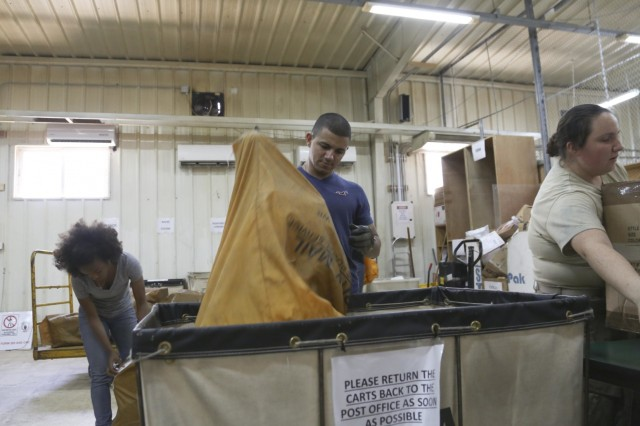 Spc. Jaime Almodovar, center, an Army Reserve mail clerk with the 4th Platoon of the 912th Human Resource Company, 90th Human Resource Company, 17th Special Troops Battalion, 17th Sustainment Brigade, 1st Sustainment Command (Theater), unloads a bag of mail at a base near Amman, Jordan, July 27, 2016.  The Soldiers deliver an average of 250 pieces of mail a day. (U.S. Army National Guard photo by Staff Sgt. Victor Joecks)