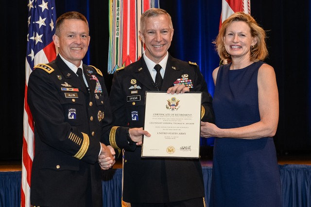 The Vice Chief of Staff of the Army, GEN Allyn, presents LTG Spoehr his certificate of retirement, along side LTG Spoehr's wife Cynthia.