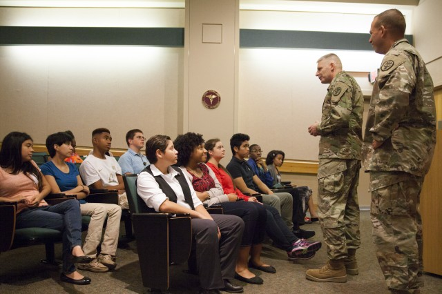 BAMC Commander Brig. Gen. Jeffrey Johnson thanks youth volunteers as Command Sgt. Maj. Albert Crews looks on during a recognition ceremony at Brooke Army Medical Center, Aug. 2, 2016.