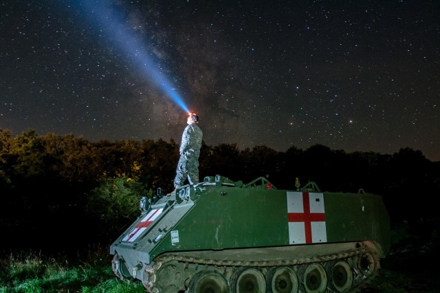 Staff Sgt. Brad Foster, a combat medic with the Oregon Army National Guard's Headquarters and Headquarters Company, 3rd Battalion, 116th Heavy Brigade Combat Team from Pendleton, Ore., looks up at the night sky from the top of an M113 medical evacuation vehicle during Exercise Saber Guardian 16 at the Romanian Land Forces Combat Training Center in Cincu, Romania, Aug. 3, 2016.