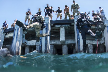 U.S. Army Pfc. Aaron Gaugler and Coast Guard diver 2nd Class Kendall Smith enter the water as part of a pier maintenance training-mission led by Navy Underwater Construction Team 2 during Rim of the Pacific 2016 at Joint Base Pearl Harbor-Hickam, Hawaii, July 12, 2016. The maritime exercise involves about 25,000 participants from 26 nations, 49 ships, six submarines and about 200 aircraft.