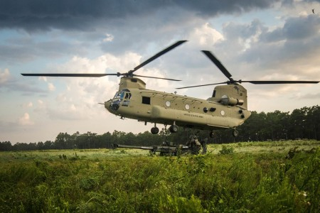 Soldiers assigned to the 82nd Airborne Division Artillery, lift the reach pendant to attach it to the cargo hook on the under belly of a CH-47 Chinook, July 19, 2016, during an exercise at Fort Bragg, N.C.