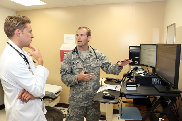 Prior to an appointment, Air Force Lt. Col. (Dr.) Nathan Evans and Kevin Forey, a Colorado University medical student, go over the patent's latest lab results. Evans is assigned to the 10th Medical Group at the U.S. Air Force Academy, but with duty at Fort Carson's Evans Army Community Hospital.(Photo by Jeff Troth)