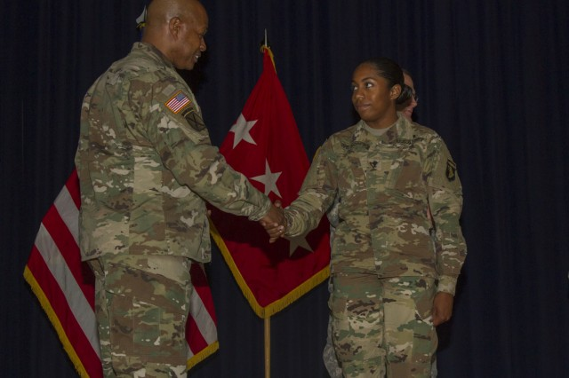 Lt. Gen. Larry D. Wyche, deputy commanding general for the United States Army Material Command, presents Spc. Iverem Wilson, a nodal network systems operator -- maintainer with 58th Signal Company, 101st Special Troops Battalion, 101st Airborne Division Sustainment Brigade, 101st Abn. Div. (Air Assault), with a coin at Wilson Theater on Fort Campbell, Ky., Aug. 9, 2016, for her outstanding performance as Distinguished Honor Graduate from the Basic Leaders Course. (U.S. Army photo by Sgt. Neysa Canfield, 101st Airborne Division Sustainment Brigade Public Affairs)