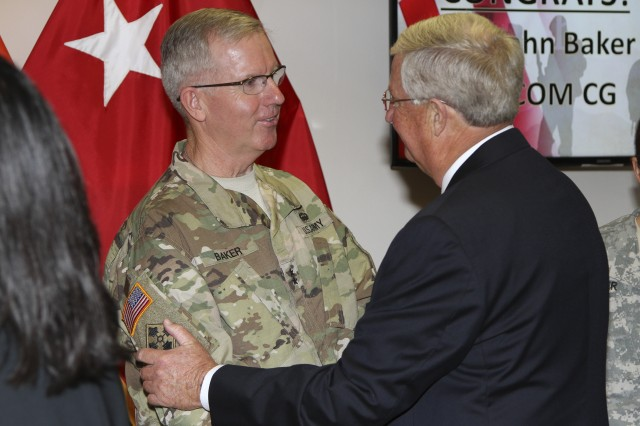 Maj. Gen. John W. Baker, new commanding general of NETCOM, receives congratulations from a former NETCOM commanding general, retired Maj. Gen. James Hylton, after the change of command ceremony August 10, at Greely Hall at Fort Huachuca, Arizona.