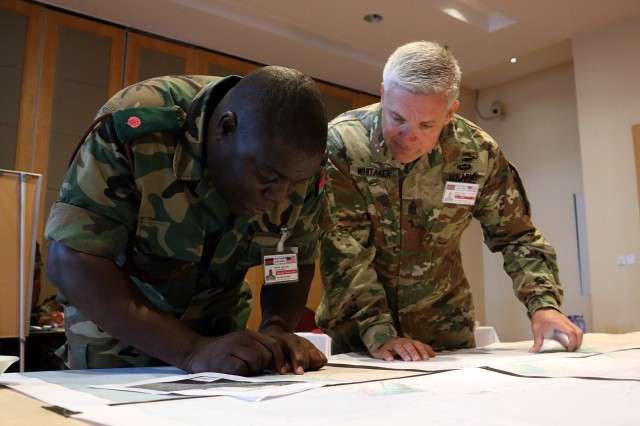 U.S. Army Command Sgt. Maj. Kevin Whitaker (right), command sergeant major of 60th Troop Command, North Carolina Army National Guard, reviews a map of villages affected by a flood during a scenario of Southern Accord 2016's disaster relief tabletop exercise. SA16 is a U.S. Army Africa-led annual, combined military exercise that brings together U.S. military personnel with African partner nations to improve readiness, promote interoperability, build capacity and strengthen partner relationships. (U.S. Army photo by Staff Sgt. Candace Mundt/Released)