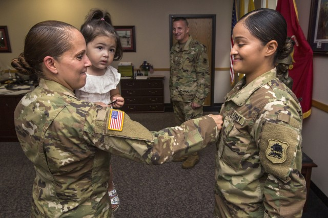Staff Sgt. Janet Medina, left, pins staff sergeant rank on her daughter, Justina Medina, during a promotion ceremony at the New Jersey Department of Military and Veterans Affairs, Lawrenceville, N.J., August 11, 2016.
