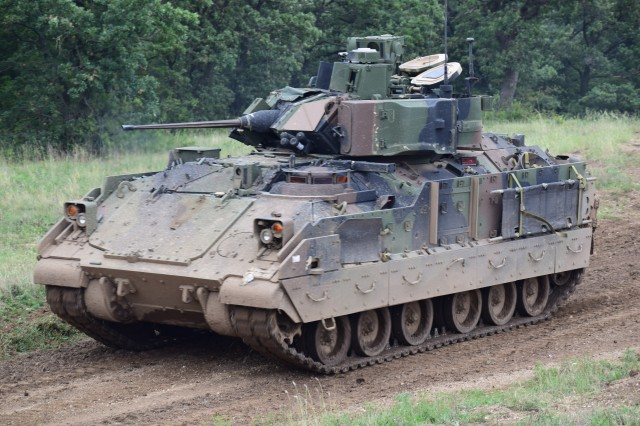 A Bradley Fighting Vehicle moves through a field to suppress targets while Hungarian infantrymen dismounts attack their objective during a Combined Arms Live Fire Exercise at Camp Ujmajor, Hungary August 11.