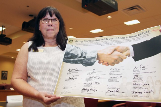 Susan Murray, Fort Sill school liaison officer, holds the symbolic, oversized APLAS agreement which was signed by about a dozen school superintendents in the Lawton-Fort Sill community, Aug. 5.