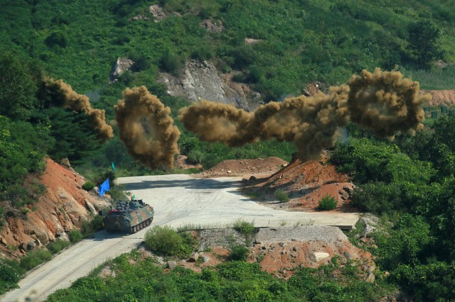 Smoke rings launched by a South Korean army K200 Infantry Fighting Vehicle burst over a training ground where earlier this month South Korean and U.S. troops practiced working as a single force to assault an objective with ground troops supported by aircraft. The smoke helps hinder the enemy's view. The training ran July 30 through Aug. 4 at a training range near Pocheon and involved U.S. troops from Company B, 2nd Battalion, 12th Cavalry Regiment, part of the 1st Cavalry Division's 1st Armored Brigade Combat Team. The brigade is on a nine-month rotational tour with the 2nd Infantry Division/ROK-U.S. Combined Division. Their Korean counterparts were from the 137th Mechanized Battalion, 16th Mechanized Brigade, 8th Infantry Division. - U.S. Army photo by Sgt. Christopher Dennis