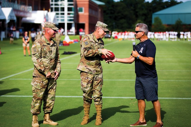 Command Sgt. Maj. Timothy Metheny, left, MCoE command sergeant major, and Maj. Gen. Eric Wesley, MCoE commanding general, receive a Falcons football as a token of appreciation presented to Fort Benning, from Steve Cannon, AMB Group CEO and graduate of West Point Class of '86.