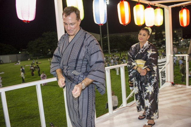Col. William B. Johnson and Command Sgt. Maj. Rosalba Dumont-Carrion, commander and command sergeant major of USAG Japan, respectively, perform the traditional Bon dance on the Bon dance tower during Camp Zama's 57th annual Bon Odori Festival held Aug. 6, attended by nearly 18,000 Japanese and American community members. (U.S. Army photo by Alia Naffouj)
