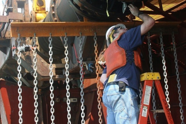 "ERDC Research Hydraulic Engineer Tim Welp checks the movement of ""tickler chains"" designed to move sea turtles out of the way of dredging activities. The chains form a curtain extending off the dredging drag arm approximately 25 feet ahead of the draghead. (US Army photo by Jon Hosaka)"