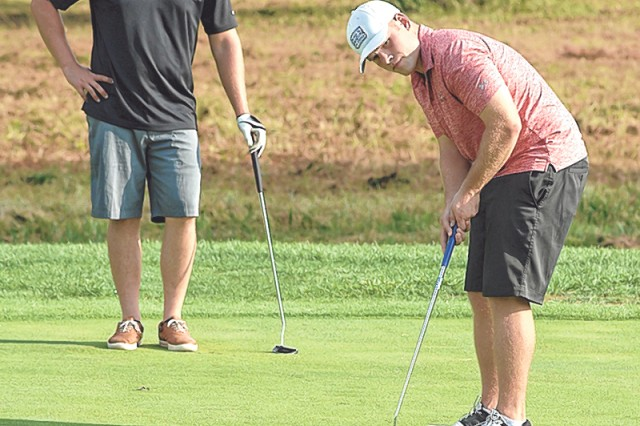 From left, Air Force Det. player Kendall Drake watches as his teammate, Patrick Gallagher, putts on the 10th green Aug. 9 at Piney Valley Golf Course during the Commander's Cup Golf Tournament.