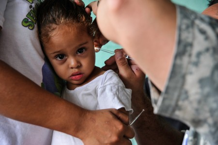 A young Honduran girl has her ear inspected by Spc. Kerry Holmes, Joint Task Force-Bravo Medical Element medic, during a Medical Readiness Training Exercise operation in Trujillo, Honduras, July 29, 2016. MEDEL conducts MEDRETEs throughout Central America to provide a variety of medical services to the local populations, who otherwise would be unable to receive medical care from licensed providers.