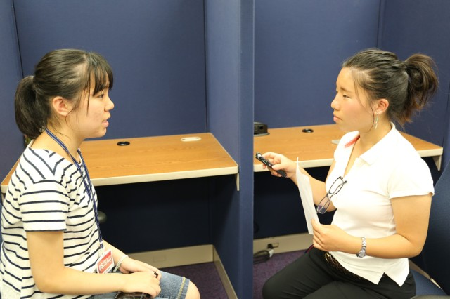 Kyoka Fujiwara, PAO intern pictured right, serves a reporter, interviewing Kanade Ueno, library intern pictured left (U.S. Army photo by Yurie Horiuchi).