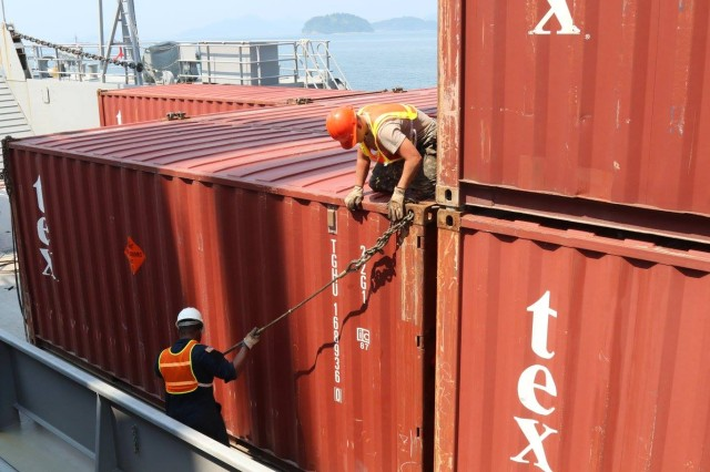 Soldiers from U.S. Army vessel Harpers Ferry secure containers to the LCU 2000's deck before sailing the load to Japan, Aug. 8.  Photo by Cpl. Sung Guk Byun.