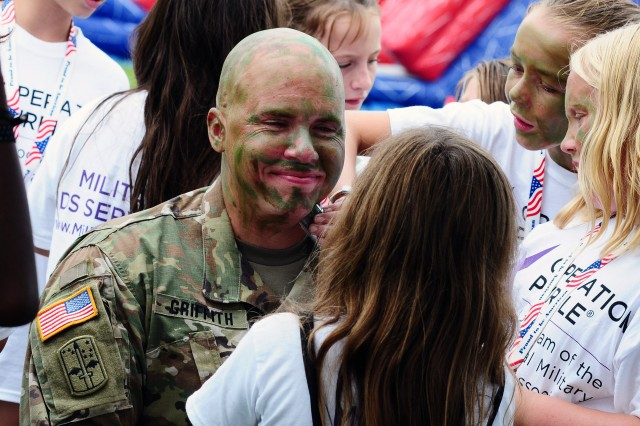 """Sgt. 1st Class Travis Griffith, with the Army Evaluation Center, smiles as campers at Operation Purple Camp at Elk Neck State Park in North East, Md. practice their camouflage painting skills during the camp's """"Military Experience Day,"""" Aug. 16, 2016. Aberdeen Proving Ground Soldiers and civilians took pause from normal mission activities to support the military children attending Operation Purple Camp and provide a Military Experience Day to remember."""