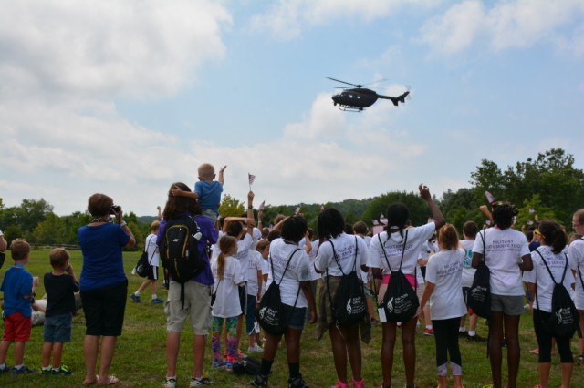 """Military children, family members and Operation Purple Camp staff wave American flags as a UH-72A Lakota helicopter prepares to land at Elk Neck State Park in North East, Md. during """"Military Experience Day"""" festivities Aug. 16, 2016. Maryland National Guard and Aberdeen Proving Ground Soldiers and civilians took pause from normal mission activities to support the military children attending Operation Purple Camp and provide a Military Experience Day to remember."""