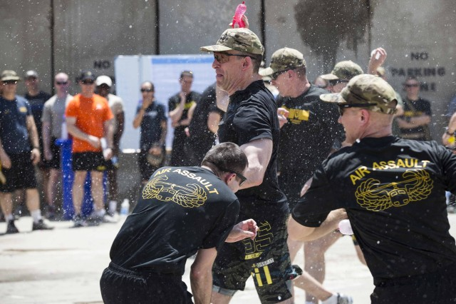 Canadian Brig. Gen. Greg Smith, center, the chief of staff for the Combined Joint Forces Land Component Command -- Operation Inherent Resolve, rears back to launch a water balloon at an opponent during the championship match and final event of the Amazing Race -- a water balloon dodge ball battle -- held Aug. 6, 2016, on Forward Operating Base Union III in Baghdad. The Amazing Race was intended to provide an opportunity to personnel stationed at Union III as part of CJFLCC-OIR to have fun and take their minds off the mission for a couple hours. The rules of the final match were set so that the Smith's team, comprised of CJFLCC leadership, could not win, so their strategy was to go down fighting.