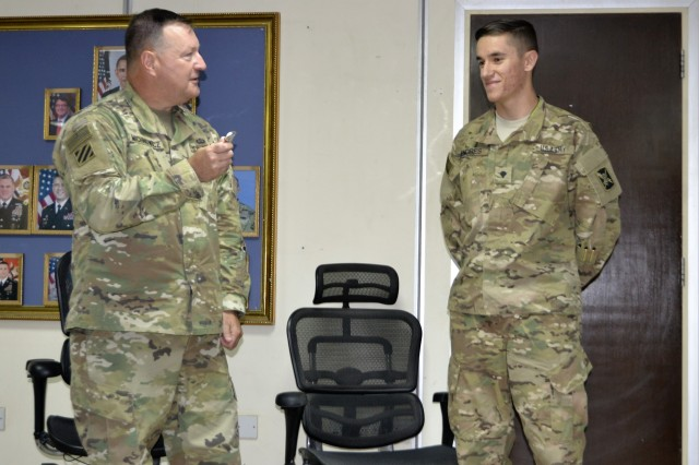 Spc. Andrew Endres, assigned as the Information Management Officer to the 297th Military Intelligence Battalion, receives a coin from Brig. Gen. Robert Michnowicz for providing systems maintenance to over 80 work stations throughout Camp Arifjan, Kuwait. SPC Endres' work ethic and technical expertise makes a successful impact to mission readiness, and he is a valued asset to U.S. Army Central Command.