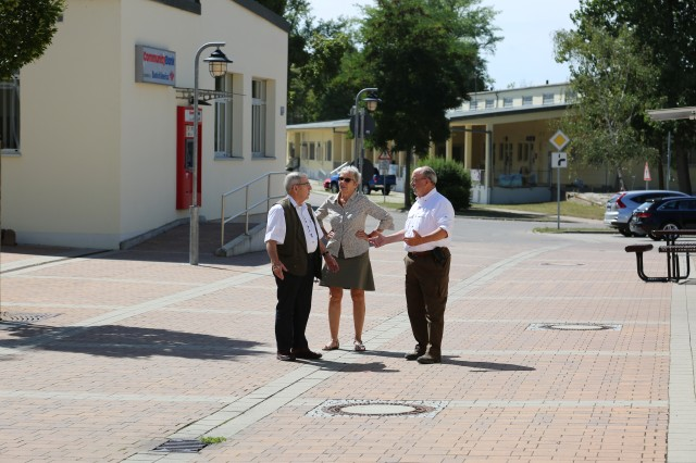 "ANSBACH, Germany (Aug. 24, 2016) -- From left, American Legion Post 1982 president Kenneth Aungst guides Diane Purnell and Enoch ""Chip"" Purnell Jr. through the Fuessgaengerzone at Storck Barracks Aug. 18. Enoch Purnell, Chip's father, was stationed at Illesheim Airfield -- what would later become part of Storck Barracks -- during the final weeks of World War II. (U.S. Army photo by Bryan Gatchell, USAG Ansbach Public Affairs)"