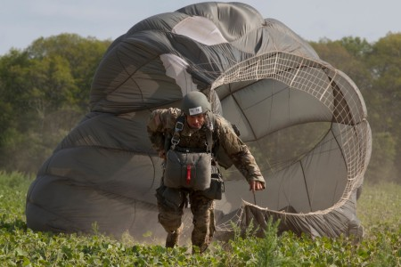 Paratrooper Warrent Officer Greg Suchanek, Special Operations Detachment (NATO) drags his parachute toward a target during Leapfest 2016 in West Kingston, R.I., Aug. 4, 2016. Leapfest is an International parachute training event and competition hosted by the 56th Troop Command, Rhode Island Army National Guard to promote high level technical training and esprit de corps within the International Airborne community.