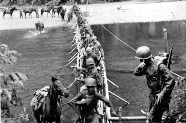 On March 18, 1944, men and animals from the 2nd Battalion cross the Tanai River on a bamboo bridge built by Kachin tribesmen, working with the Office of Strategic Services, near the village of Ning Awng.