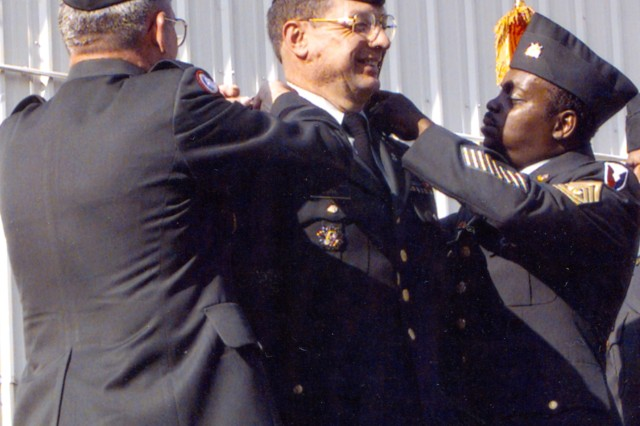 Maj. Gen. Beauchamp, commander of the Tank-automotive and Armaments Command, and Command Sgt. Maj. Herbert Nicholson change the crests on the uniform of Col. Greg Potts, commander of Anniston Army Depot from 1997-1999 during the October 1998 Change of Management ceremony when ANAD was transferred under the command of TACOM.