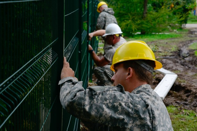(From front to back) U.S. Army Spc. Kyle West U.S. Army Spc. Jimmy Martin and U.S. Army Spc. Nick Skirchak, assigned to the 375th Engineer Company, 467th Engineer Battalion, 926th Engineer Brigade, 412th Theater Engineer Command, assist with constructing a fence during a Humanitarian Civil Assistance (HCA) project in Sauliai, Lithuania, Aug. 18, 2016. As part of the European Command's (EUCOM) Humanitarian and Civic Assistance Program, the 375th Engineer Company, 457th Civil Affairs Battalion and the Lithuanian military collaborate to renovate the fence at Kudikiu Namai, an orphanage for Lithuanian children up to the age of 6, in Sauliai, Lithuania, August 8-26, 2016. The Humanitarian and Civic Assistance Program is a series of medical and engineering engagements in several European countries in support of strategic, theater, operational and tactical objectives. (U.S. Army photo by Pfc. Emily Houdershieldt)