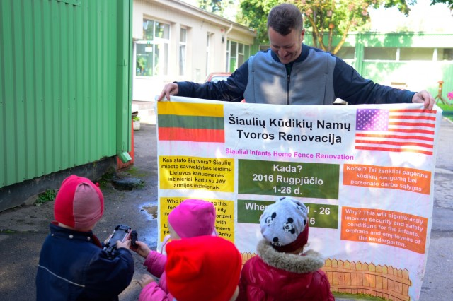 U.S. Army 1st Lt. John Sorich, assigned to Alpha Company, 457th Civil Affairs Battalion, 361st Civil Affairs Brigade, 7th Mission Support Command, shows a sign created by the Civil Affairs team to the children from Kudikiu Namai during a Humanitarian Civil Assistance (HCA) project in Sauliai, Lithuania, Aug. 19, 2016. As part of the European Command's (EUCOM) Humanitarian and Civic Assistance Program, the 375th Engineer Company, 457th Civil Affairs Battalion and the Lithuanian military collaborate to renovate the fence at Kudikiu Namai, an orphanage for Lithuanian children up to the age of 6, in Sauliai, Lithuania, August 8-26, 2016. The Humanitarian and Civic Assistance Program is a series of medical and engineering engagements in several European countries in support of strategic, theater, operational and tactical objectives. (U.S. Army photo by Pfc. Emily Houdershieldt)