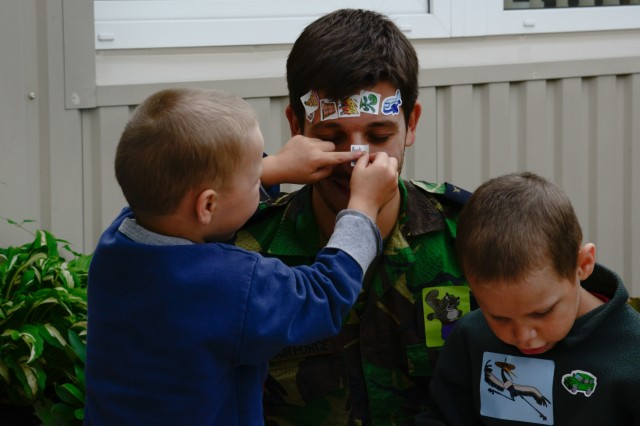 A Portuguese airman plays with children from Kudikiu Namai during a Humanitarian Civil Assistance (HCA) project, in Sauliai, Lithuania, August 23, 2016. As part of the European Command's (EUCOM) Humanitarian and Civic Assistance Program, the 375th Engineer Company, 457th Civil Affairs Battalion and the Lithuanian military collaborate to renovate the fence at Kudikiu Namai, an orphanage for Lithuanian children up to the age of 6, in Sauliai, Lithuania, August 8-26, 2016. (U.S. Army Photo by Pfc. Emily Houdershieldt)